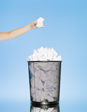 blue bin: Hand trowing a paper into a wastebasket on blue background Stock Photo