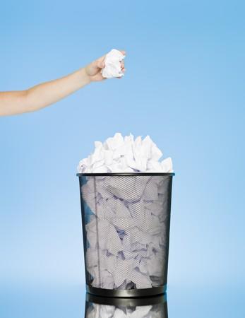 Hand trowing een papier in een prullen bak op blauwe achtergrond