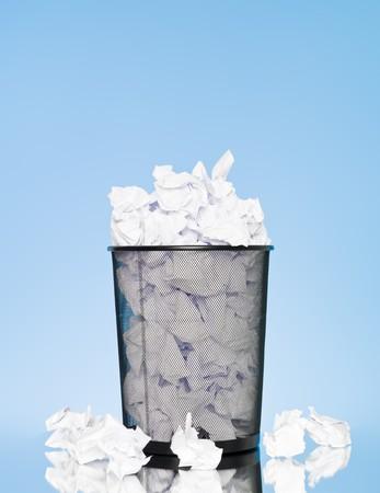 Filled wastebasket on blue background photo