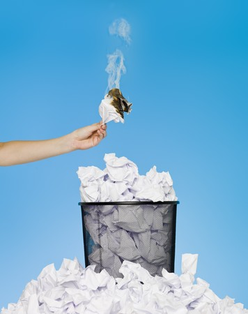 wastebasket: Hand holding a piece of paper in flames over a wastebasket
