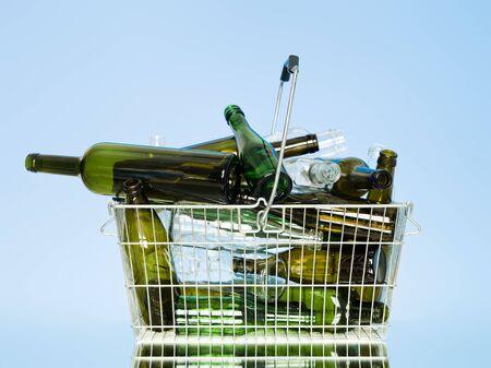 wastebasket: Empty glass bottles in a wastebasket on blue background Stock Photo