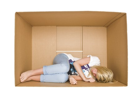claustrophobia: Woman sleeps in a cardboard box isolated on white background