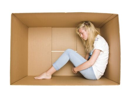 trapped: Woman siting in a cardboard box isolated on white background