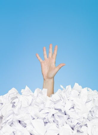 office chaos: Human hand buried in white paper