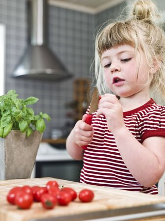 Young girl cutting tomatoes in the kitchen Stock Photo - 7199497