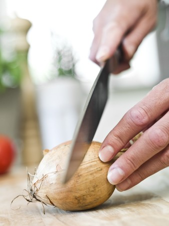 short focal depth: Human cutting onion in the kitchen