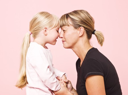 Mother and daughter on pink background photo