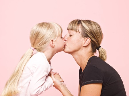Mother and daughter kissing towards pink background Stock Photo - 7570667