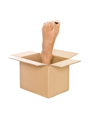 Human foot in a cardboard box isolated on white background photo