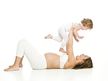 Pregnant woman with her daughter laying on the floor isolated on white background Stock Photo - 7671016