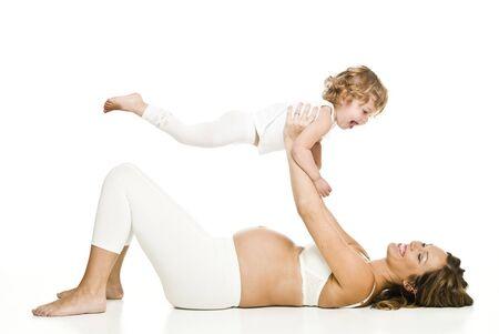 frau sitzt am boden: Schwangere Frau mit ihrer Tochter isoliert auf wei�em Hintergrund