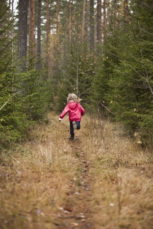 Little girl running in the forest photo