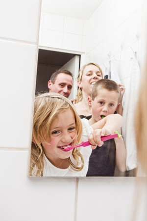 Family brushing teeths in the bathroom