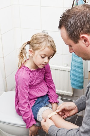 bandage: Father put on band-aid on daughters knee Stock Photo