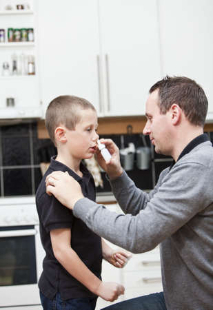 Man giving nose drops to young boy photo