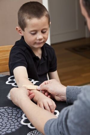 Man puting Band-Aid on sons arm