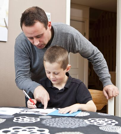 Father helping son with his homework sitting in at the table Stock Photo - 8168737