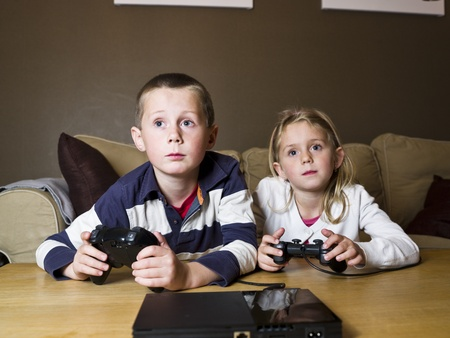 handheld computer: Siblings playing Video Games sitting in the sofa Stock Photo