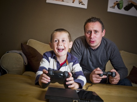 Father and son playing Video Games sitting in the Sofa Stock Photo - 8308547