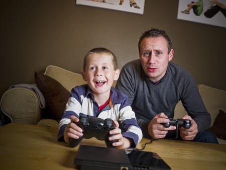 jugando videojuegos: Padre e hijo jugando juegos de video, sentado en el sof�