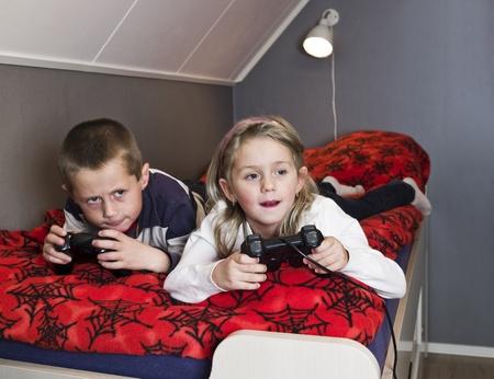ni�os jugando videojuegos: Hermanos jugando juegos de video lieing en la cama Foto de archivo