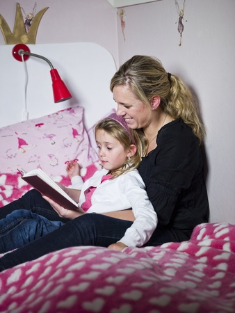 nanny: Mother and Daughter storytelling sitting in the bed Stock Photo