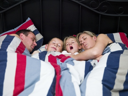 Family sleeping in the same bed photo