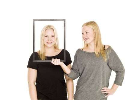 Girl holding a frame in front of her friends face Stock Photo - 8308546