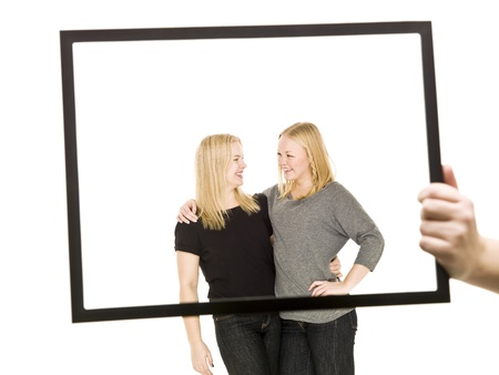 Two blond girls in a frame isolated on white background Stock Photo - 8308549