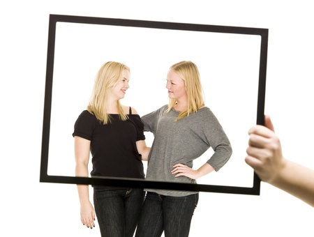 Two blond girls in a frame isolated on white background Stock Photo - 8308540