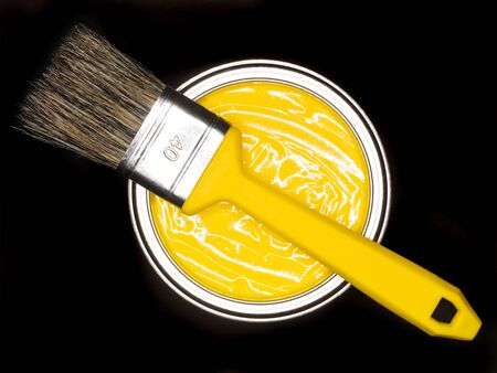 Yellow Paint can and brush from above on black background Stock Photo - 8625060