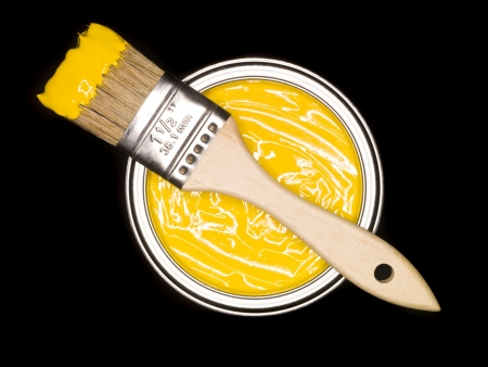brush paint: Yellow Paint can and brush from above on black background