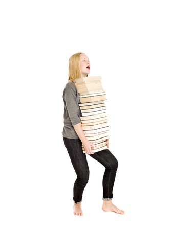Young girl carrying a heavy pile of books isolated on white background photo