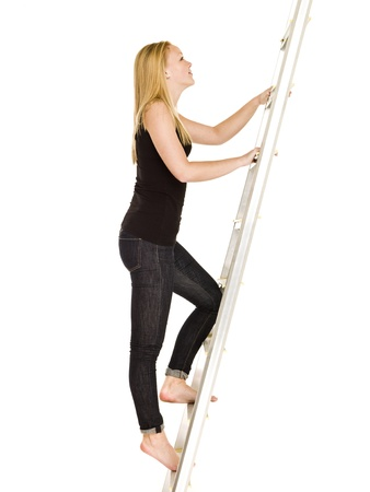 Woman climbing up the ladder isolated on white background photo