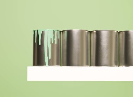 Paintcans in a row on green background photo