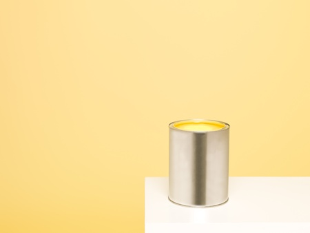 paintcan: Paintcan with spill on yellow background Stock Photo