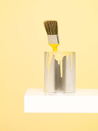 paintcan: Paintcan and Paintbrush with spill on yellow background Stock Photo