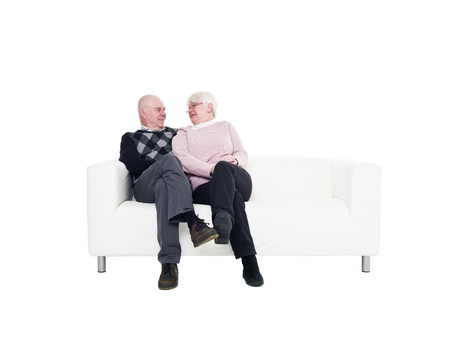 Older couple in a sofa isolated on white background photo