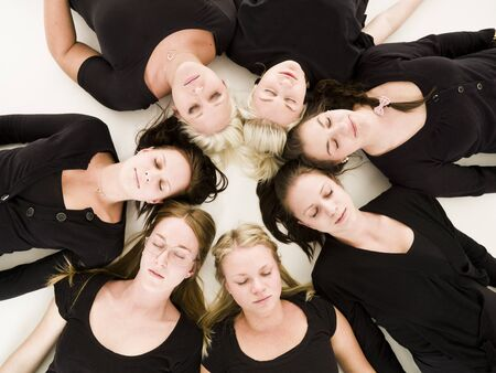 Group of Young Women with closed eyes lieing in a circle on white background Stock Photo - 9193980