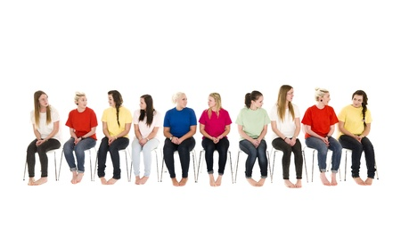 Group of Young women sitting on chairs wearing colorfull t-shirts Stock Photo - 9189702