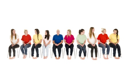 people sitting: Group of Young women sitting on chairs wearing colorfull t-shirts