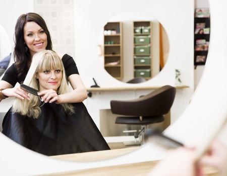 Friseur in Aktion mit blond Kunden Standard-Bild