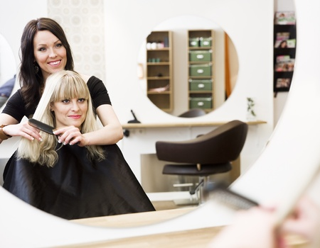 hair salon: Hairdresser in action with blond customer