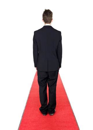 Man from behind on a red carpet isolated on white background photo