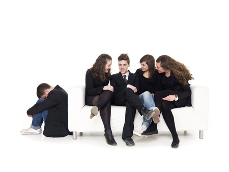 Four people in a sofa rejecting a guy isolated on white background photo