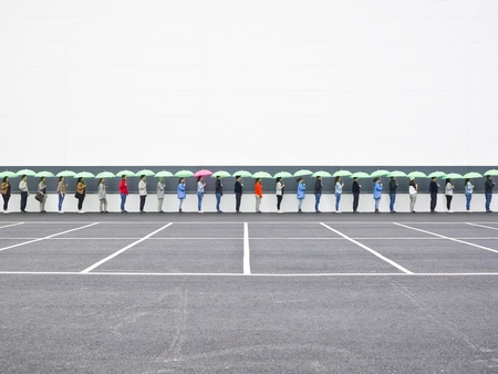 People with umbrellas waiting in line Stock Photo - 10696348