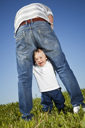 Young boy playing around his fathers legs photo