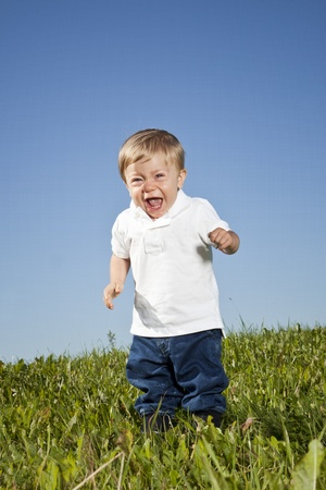 Crying child standing in the grass photo