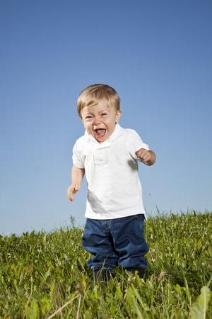 enfant qui pleure: Debout enfant qui pleure dans l'herbe