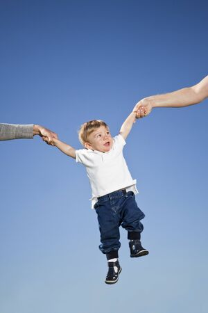 Child hanging in the air between parents hands photo